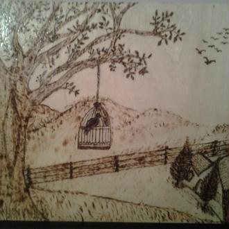 Creation pyrogravure sur bois un oiseau dans une cage et un beau paysage